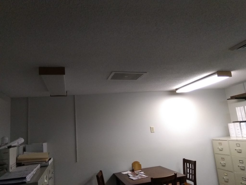 picture of room with only one working fluorescent fixture